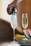 Hand pours champagne into tall glasses - 238569156