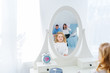 Baby girl with long hair looking at her reflection in a white room with mirror. Mother and father is in reflection