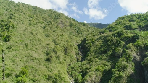 Aerial view of waterfall in the mountains of Filipino cordillera. Waterfall in the mountains. waterfall flowing on the slopes of mountains covered with tropical vegetation. Philippines, Luzon
