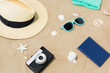 vacation, travel and tourism concept - vintage camera, passport, hat and sunglasses on beach sand