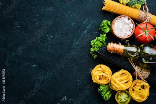 Assortment of dry pasta with ingradients on the old background. Top view. Free copy space.