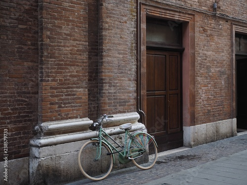 Ferrara, Italy. Bicycle resting on the facade of a building.