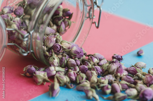 Rose bud tea in a jar. Herbal tea on pink and blue background, selective focus