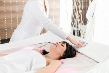 Beautiful girl on Spa procedure in Spa salon lying on the massage bed white, the specialist clicks on the button choosing massage mode © pantovich