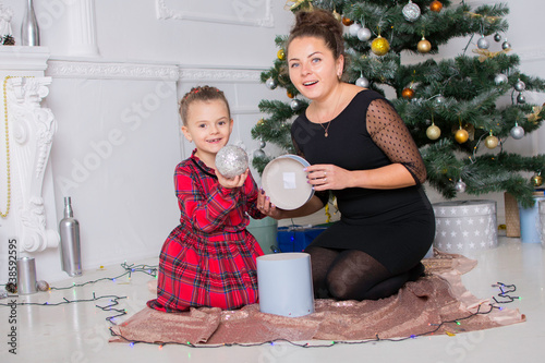 Foto Murales mom and daughter open gifts in Christmas tree near Christmas eve