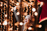 Young happy woman with Christmas light on the street - 238604325