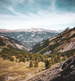 Single mountain biker riding into immense Alpine mountain range