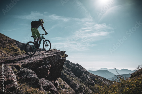 mountain biker on a large rock deep in the alps with sun and mountain layers behind