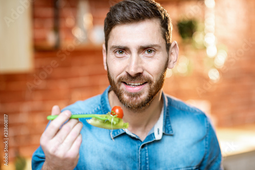 Foto Murales Close-up portrait of a handsome man eating healthy salad on the kitchen at home