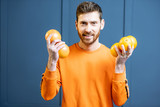 Colorful portrait of a caucasian bearded man in orange sweater holding fruits on the blue background