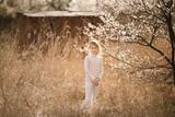 Blonde girl in the blossom garden. Spring background with white flower - 238611107