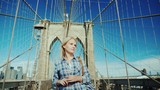Attractive woman walks on the Brooklyn Bridge on a clear summer day - 238617935