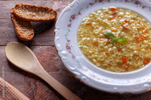 Foto Murales Jardiniere soup in porcelain dish, wooden spoon and toast