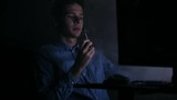 young cute man vaping in front of computer at home in dark room - 238628101