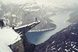 Trolltunga cliff under snow in Norway. Scenic Landscape. Man traveller standing on edge of rock and looking down. Travel, extreme and active lifestyle.