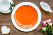 Leinwanddruck Bild - Simple color table setting for celebration with roses, orange plates and heart-shaped saucers on wooden table background top view mock up