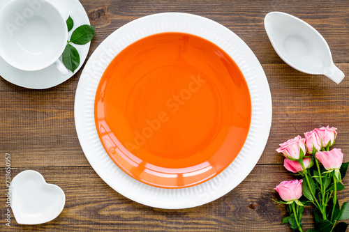 Leinwanddruck Bild Simple color table setting for celebration with roses, orange plates and heart-shaped saucers on wooden table background top view mock up