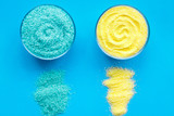 Colorful bath salt blue and yellow on blue background top view