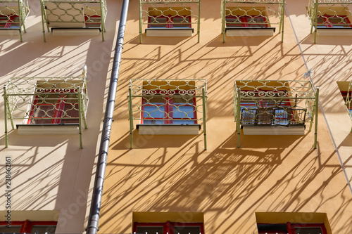 obraz lub plakat Facade of a residential building with small balconies in front of the window
