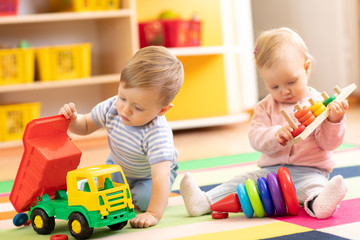 Kids playing with educational toys. Children sit on a rug in a play room at home or kindergarten. Toddler boy with toy lorry and baby girl with rings. © Oksana Kuzmina