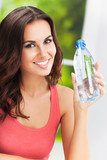 Portrait of young cheerful woman with bottle of water