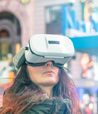 Mesmerized young woman wearing VR Glasses at night in Times Square, Manhattan - 238689195