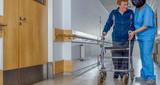 Nurse assisting elder people in a rehab facility gym - 238689349