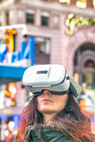 Mesmerized young woman wearing VR Glasses at night in Times Square, Manhattan - 238689752