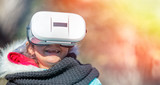 Happy young girl wearing VR glasses exploring city park in winter - 238689760
