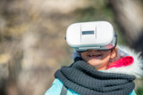Happy young girl wearing VR glasses exploring city park in winter - 238690761