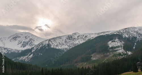 Awesome Mountains Ridge with Snow, Sun, Forest and Clouds driven by Strong Wind