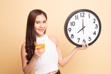 Asian woman with a clock drink orange juice. - 238696173