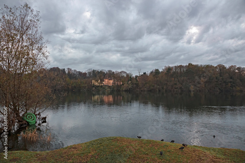Foto Murales Panoramic view of the Ticino river with clouds and trees that are reflected in its clear water, on a winter day at sunset.