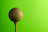 Close-up the shady side of a golf ball on a tee. Copy space. Bright green salad background.