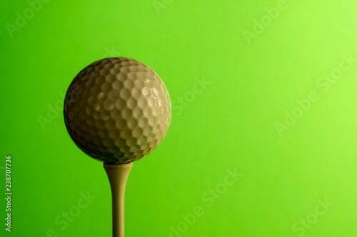 Close-up the shady side of a golf ball on a tee. Copy space. Bright green salad background. - 238707736