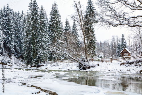 Foto Murales frozen mountain river in spruce snowy forest, fence and arbor on the bank