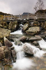 Rustic bridge over a mountain cascade at Cwm Idwal in the Glyderau range of mountains in Snowdonia National Park North Wales © David Pimborough