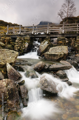 Fototapeta Rustic bridge over a mountain cascade at Cwm Idwal in the Glyderau range of mountains in Snowdonia National Park North Wales