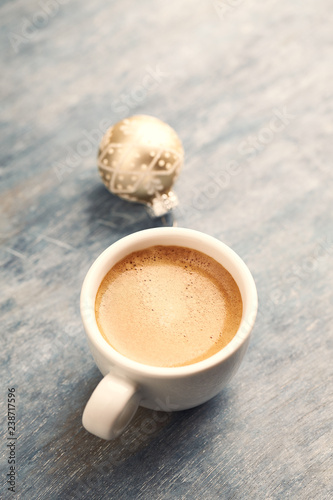 Cup of coffee and a Christmas bauble. Christmas time. Rustic wooden background. Copy space.