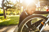 Attractive fit sportswoman having to fix her bicycle at the park