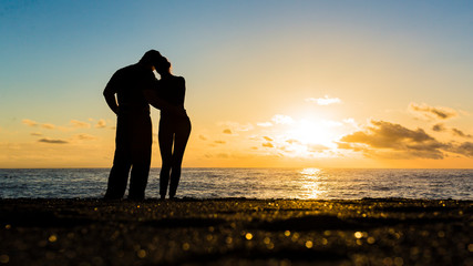 Silhouette of loving couple standing riverside and beautiful sunset background © Stavros