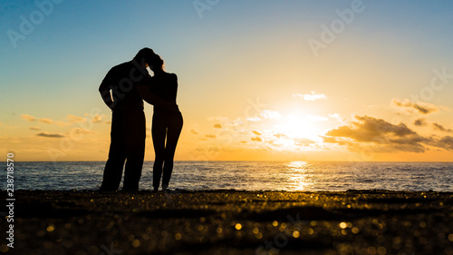 Silhouette of loving couple standing riverside and beautiful sunset background