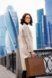 businesswoman in a bright coat and a wooden case