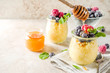 Leinwanddruck Bild - Healthy diet good ideas, sweet breakfast polenta in portioned jars with fresh frozen berries and honey, beige stone background copy space top view