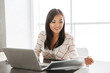Image of young asian woman 20s working on laptop, while sitting at table in flat