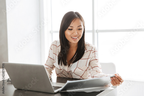 Image of young asian woman 20s working on laptop, while sitting at table in flat © Drobot Dean