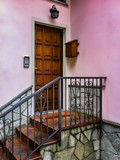 staircase to a wooden door on pink building