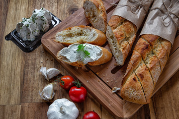 Sliced French baguette with cottage cheese, tomatoes and garlic on wooden background