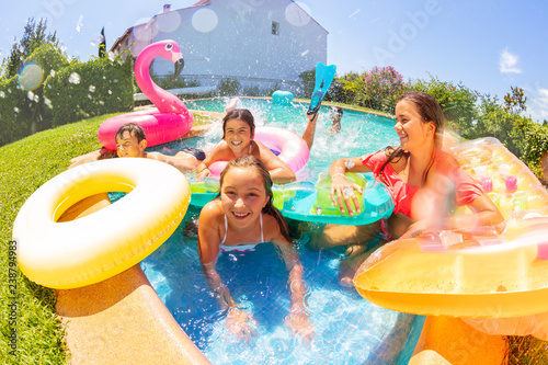 Joyful friends playing in outdoor swimming pool