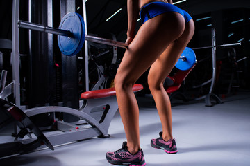 Close-up girl's legs doing exercises while holding barbell in the gym.